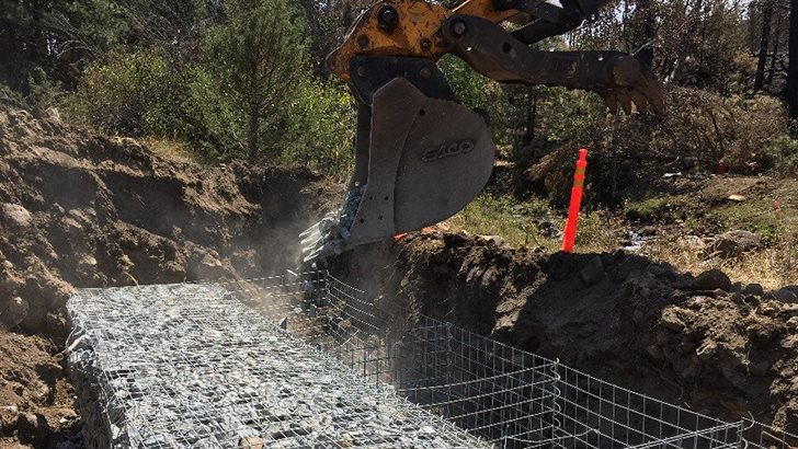"""Placing mechanically stabilized earth """"baskets"""" and filling with crushed rock to form an abutment for the bridge. (USDA photo by Chris Bielecki)"""