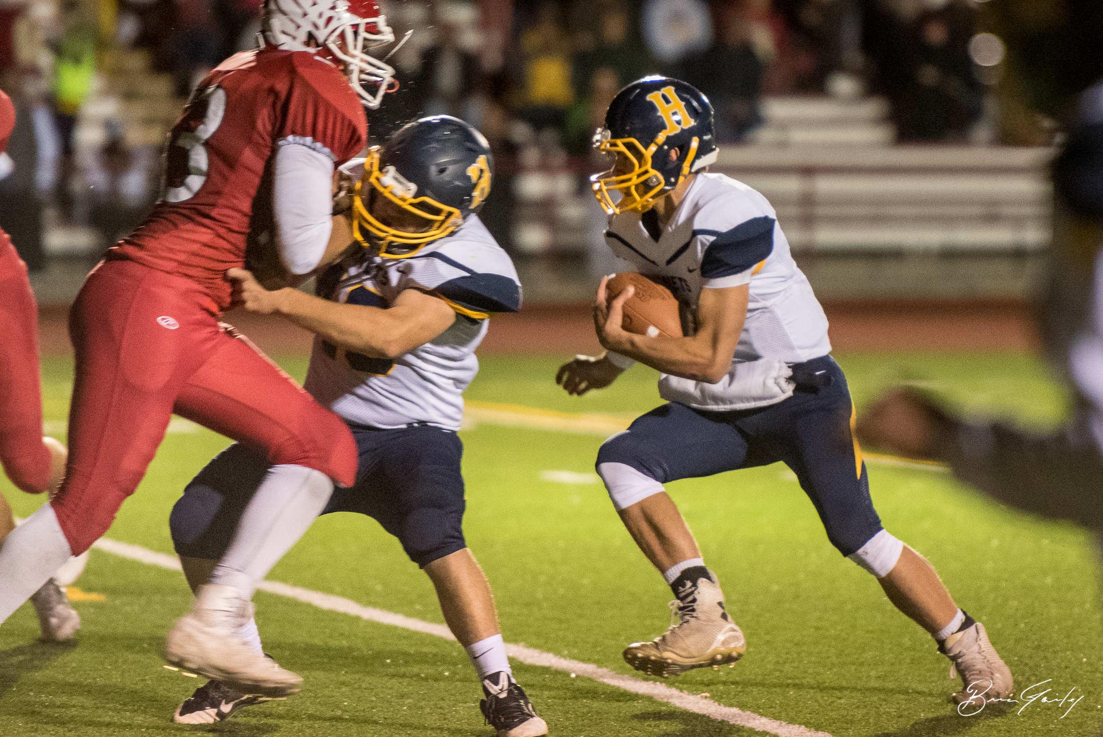 Henley QB #7, Kyle Hadwick holds onto the ball after the option play.