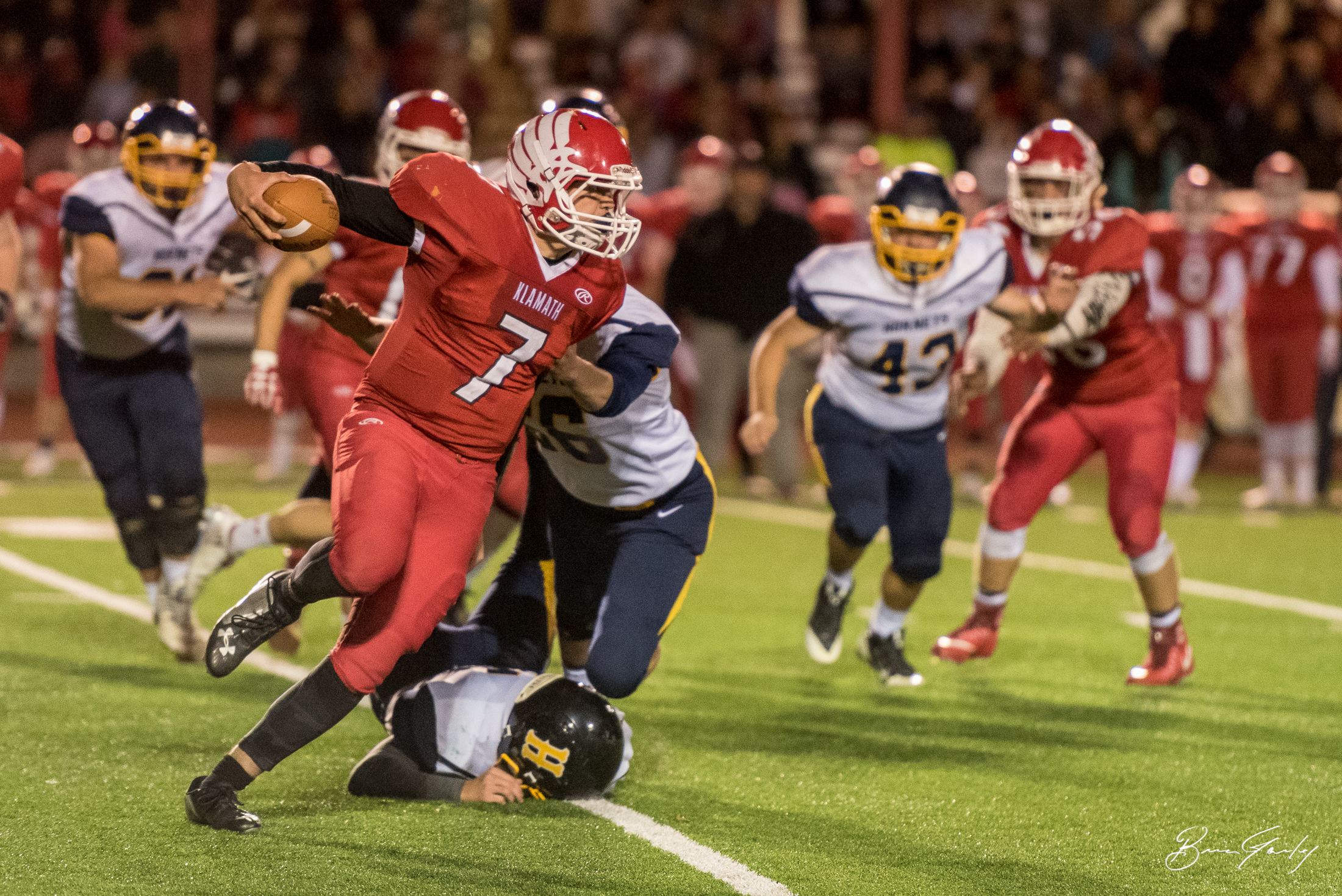 The starting QB for Klamath Union #7, Izak Peterson keeps the ball on this play and scrambles for a first down.