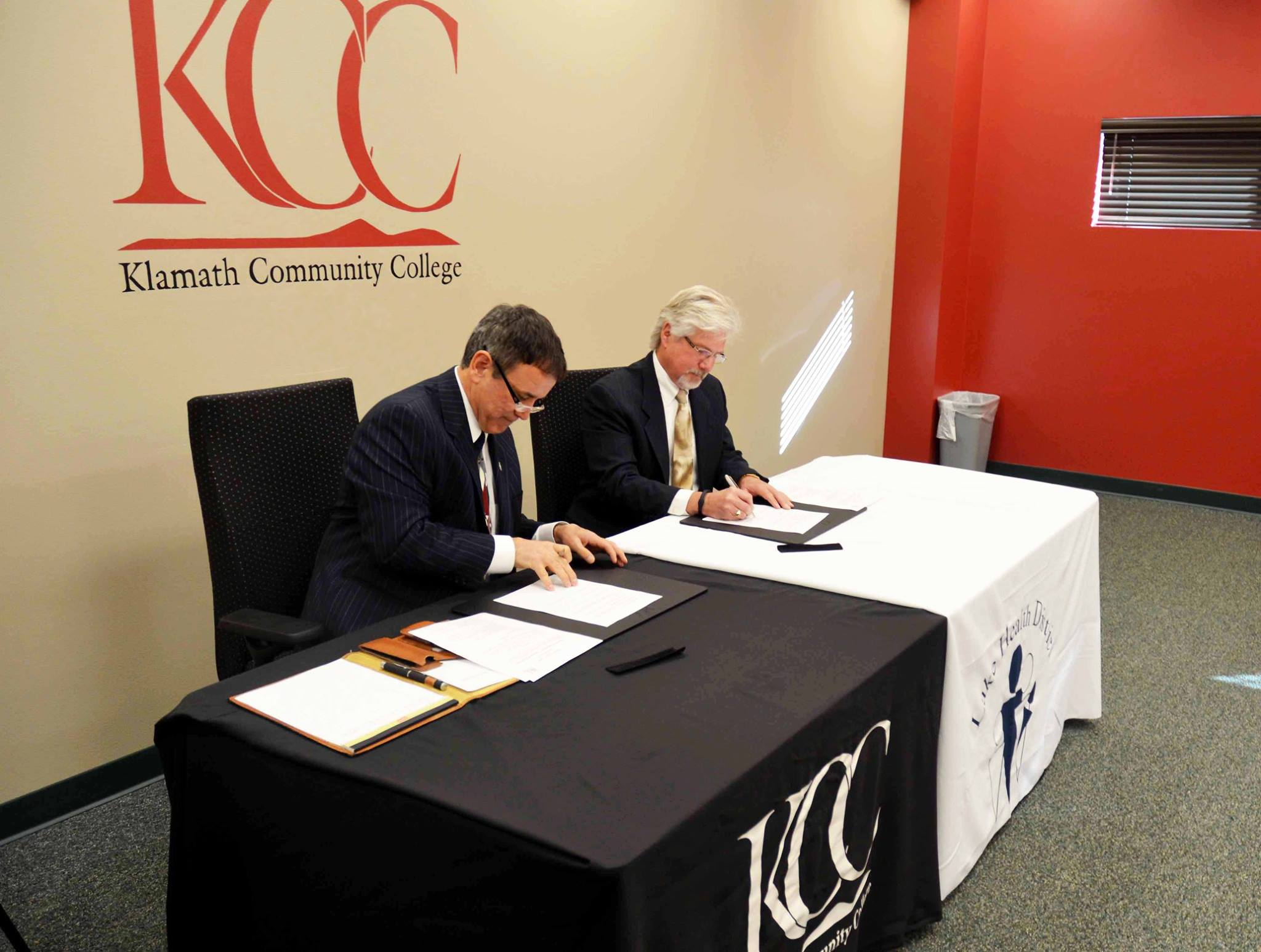 Klamath Community College President Dr. Roberto Gutierrez (left) and Lake Health District CEO Charlie Tveit sign an agreement for services in Oct. 2013. The agreement set the foundation for KCC's nursing program.