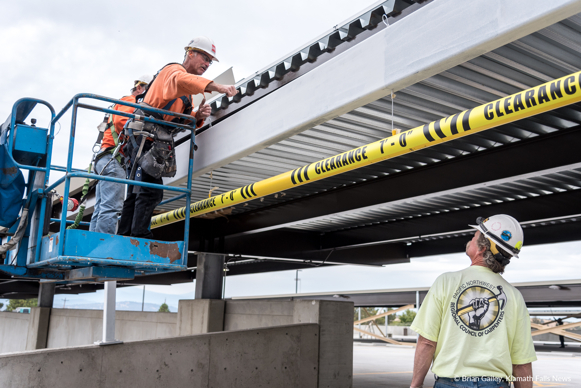 Contractor Mark McKean [center] and crewmen from Perlo Construction add a rain gutter to the roof over the ramp to the upper deck of the new parking garage of Sky Lakes Medical Center. (Brian Gailey)