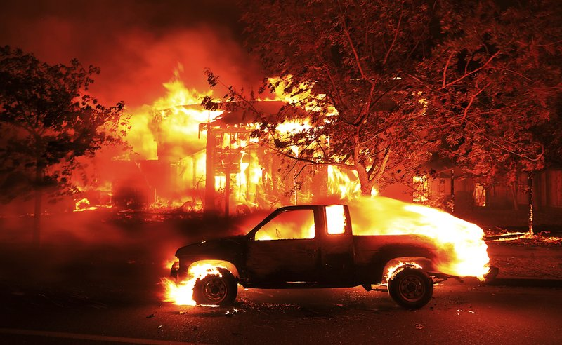 Coffey Park homes burn early Monday Oct. 9, 2017 in Santa Rosa, Calif. More than a dozen wildfires whipped by powerful winds been burning though California wine country. (Kent Porter/The Press Democrat via AP)