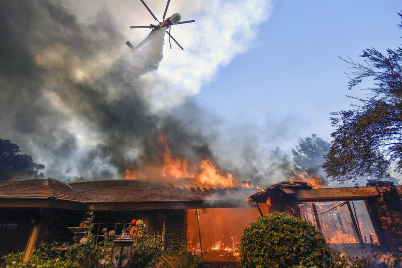 A helicopter dumps water on a home as firefighters battle a wildfire in Anaheim Hills in Anaheim, Calif., Monday, Oct. 9, 2017. (Jeff Gritchen/The Orange County Register via AP)