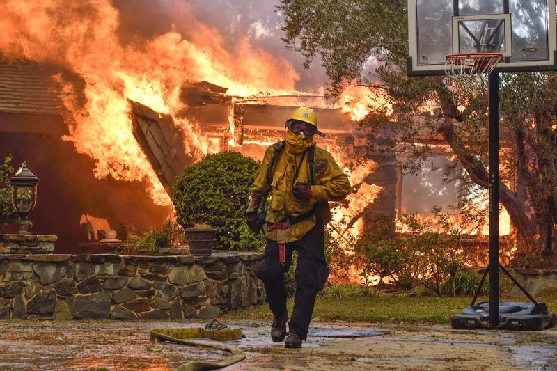 Firefighters work to extinguish a fire at a home as they battle a wildfire in Anaheim Hills, Calif., Monday, Oct. 9, 2017. (Jeff Gritchen/The Orange County Register via AP)