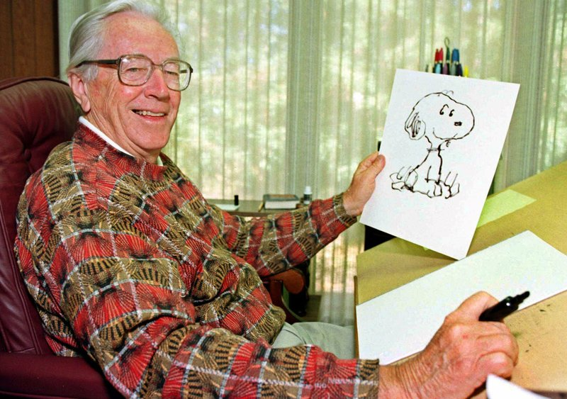 """FILE - In this Feb. 12, 2000, file photo, cartoonist Charles Schulz displays a sketch of his beloved character """"Snoopy"""" in his office in Santa Rosa, Calif. The home of """"Peanuts"""" creator Schulz burned to the ground in the deadly California wildfires but his widow escaped, her stepson said Thursday, Oct. 12, 2017. Jean Schulz, 78, evacuated before flames engulfed her hillside home Monday and is staying with a daughter, Monte Schulz said. (AP Photo/Ben Margot, File)"""