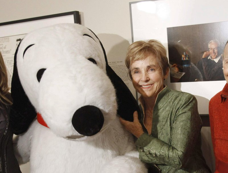 """FILE - In this Oct. 1, 2010, file photo, """"Peanuts"""" creator Charles M. Schulz' widow, Jean Schulz, stands with the character """"Snoopy"""" during the installation of a portrait of Schulz by photographer Yousuf Karsh, at the National Portrait Gallery, in Washington, D.C. The home of Charles Schulz burned to the ground in the deadly California wildfires but his widow escaped, her stepson said Thursday, Oct. 12, 2017. Jean Schulz, 78, evacuated before flames engulfed her hillside home Monday and is staying with a daughter, Monte Schulz said. (AP Photo/Jacquelyn Martin, File)"""