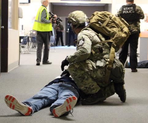 In this Active Shooter Drill, a First Responder examines a casualty. Victims were played by actors. (Image: Samantha Tipler)