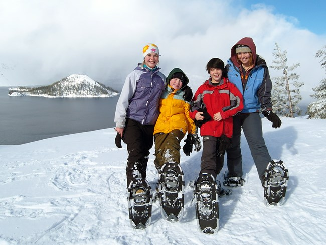 Kids pose in front of Crater Lake on a ranger-guided snowshoe walk (NPS)
