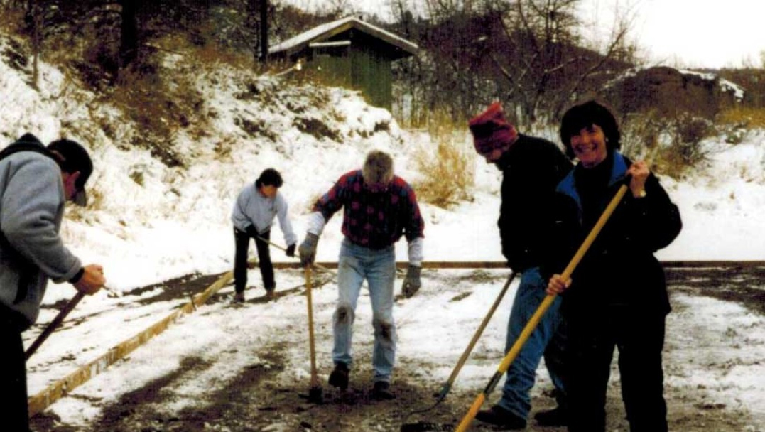 In the late 1990's, volunteers raking the sand and leveling it prior to putting down the plastic liner. Led by our very own Paulamom - right-hand side.(KlamathIceSports.org)