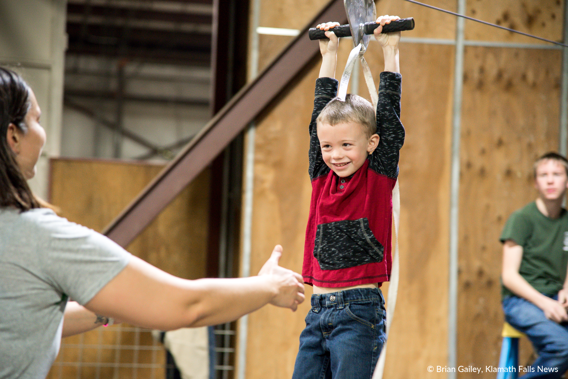 Braydon Henderson grins and giggles as he slides down the Boy Scouts zip line at PLAY Outdoors, Klamath Falls, Ore. - January 20, 2018 (Brian Gailey)