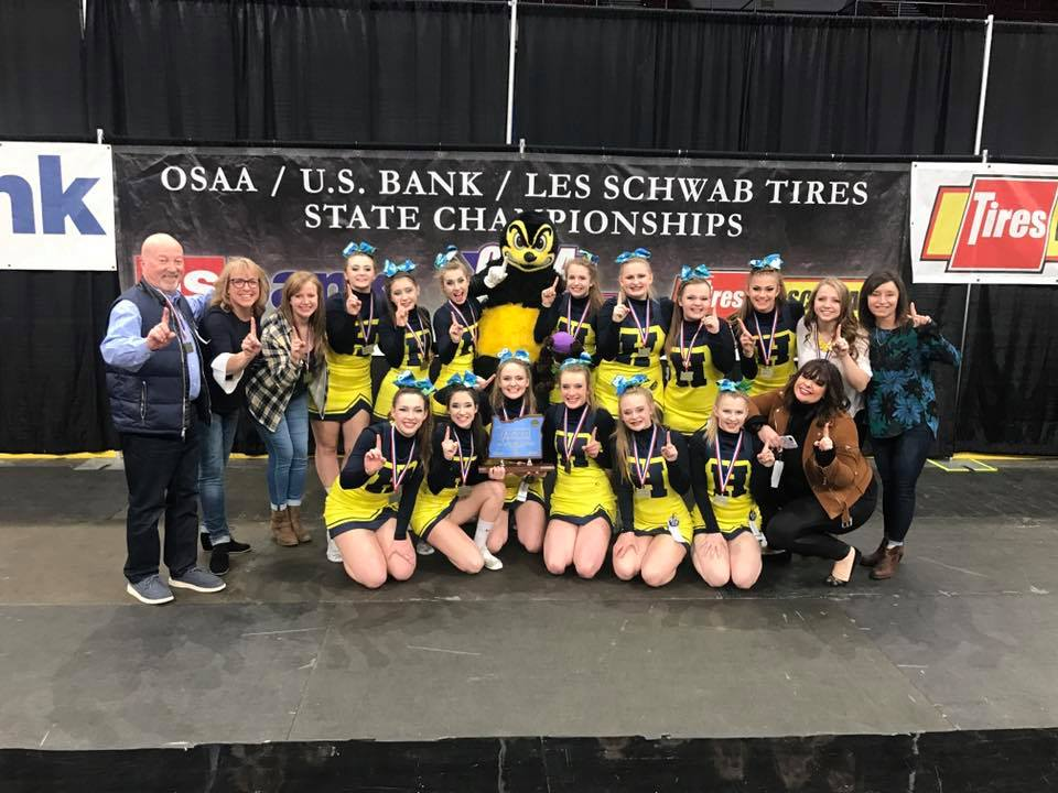 Henley High School Cheer posing with the State Championship Trophy after winning the 2018 OSAA Cherleading State Championships. (Image - Facebook: Henley Cheer)