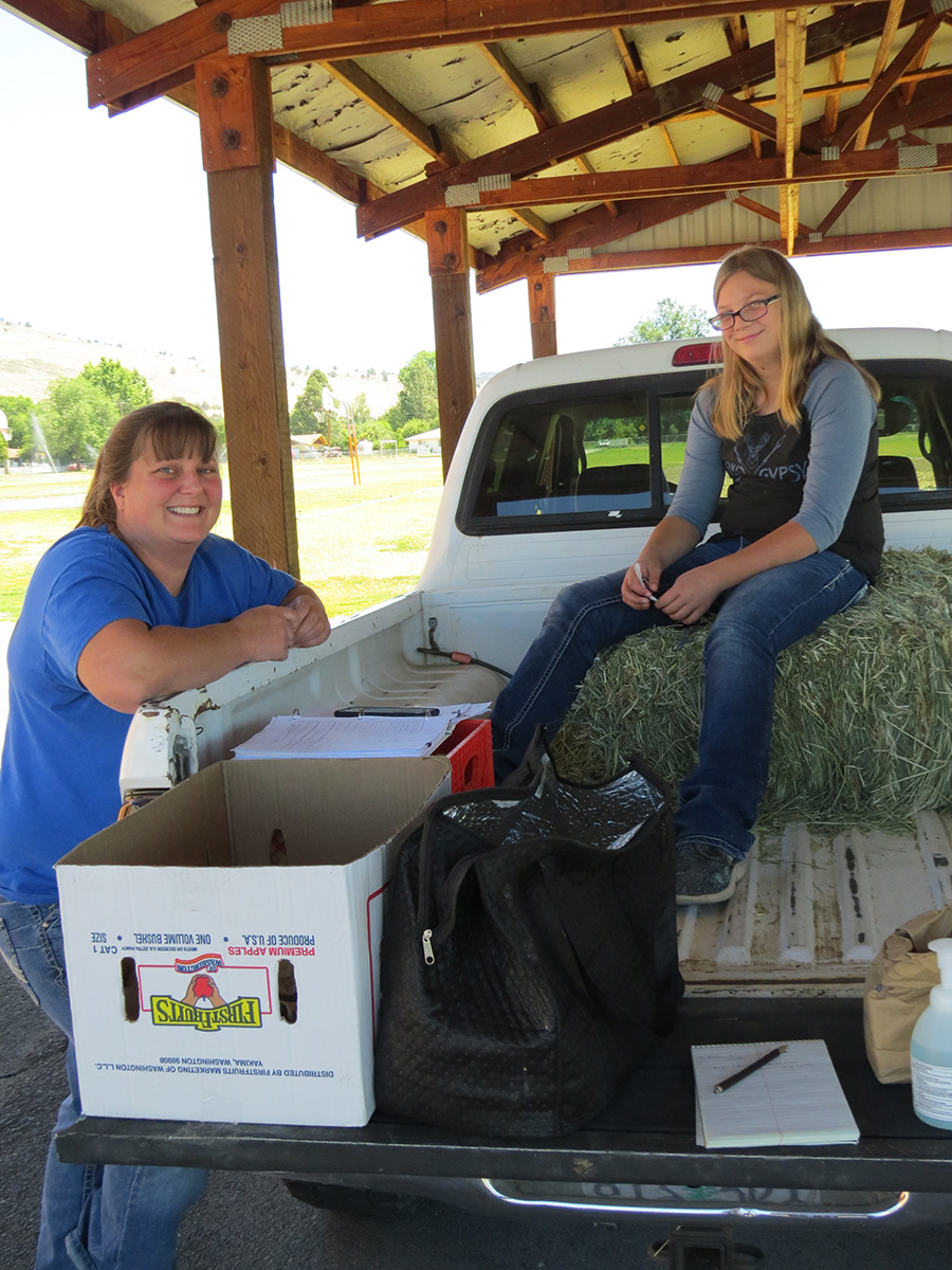Jen Gladwill and her daughter, Audrey, who will be an eighth grader at Henley Middle School this fall, hang in the back of their pickup truck after handing out free sack lunches to kids who showed up at Ferguson Elementary School between 11 a.m. and noon. (Marcia Schlottman, KCSD)