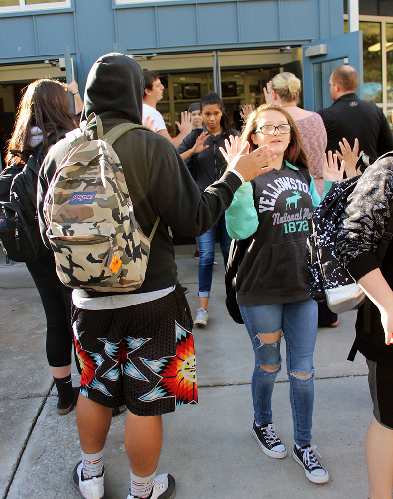 Chiloquin Junior-Senior High School leadership students hold doors and give classmates hand slaps and high-fives as they leave the school at the end of the day. The students hold the doors and greet classmates in the morning as well.