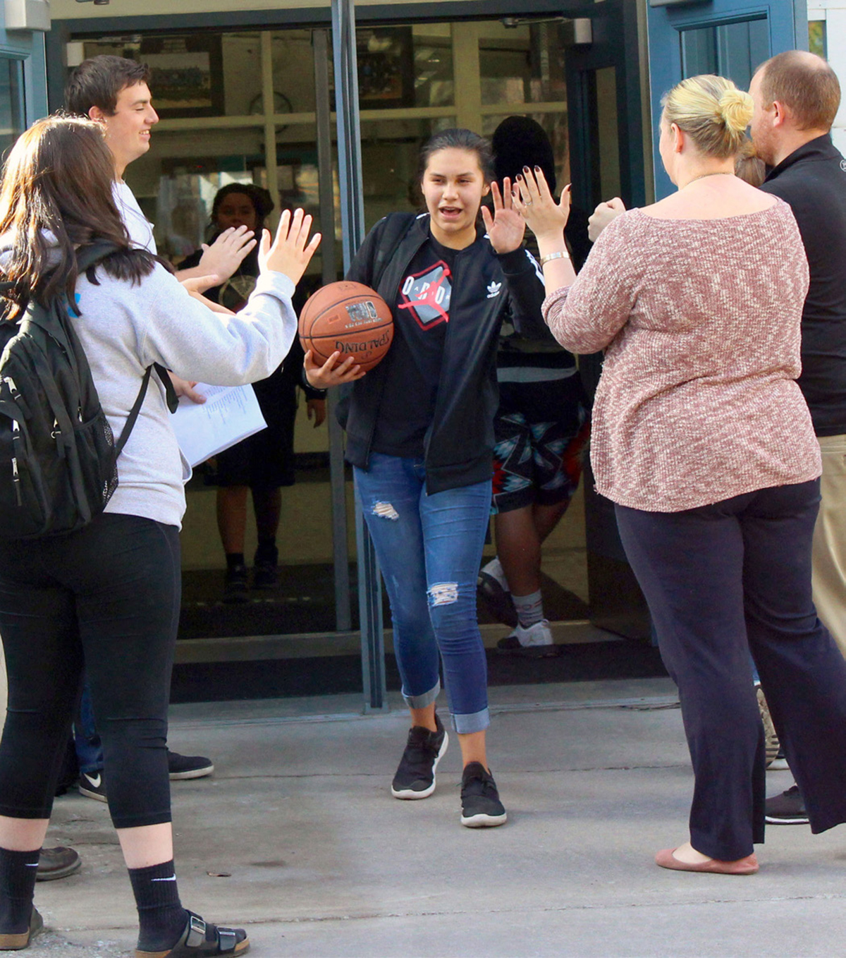 Junior-Senior High School leadership students hold doors and give classmates hand slaps and high-fives as they leave the school at the end of the day. The students hold the doors and greet classmates in the morning as well.