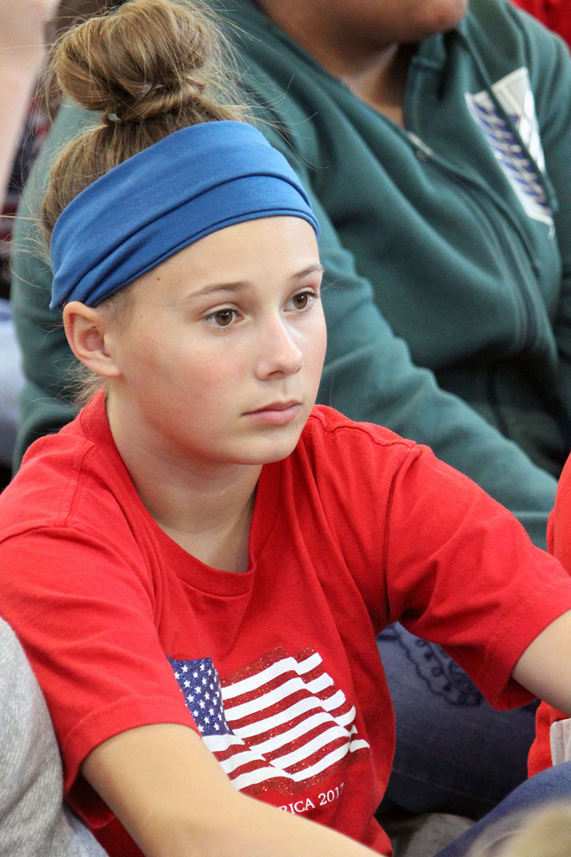 Peterson Elementary School sixth-grader Kate Mathis on Friday sports a blue headband and a red shirt with the American flag in honor of the Veterans Day.