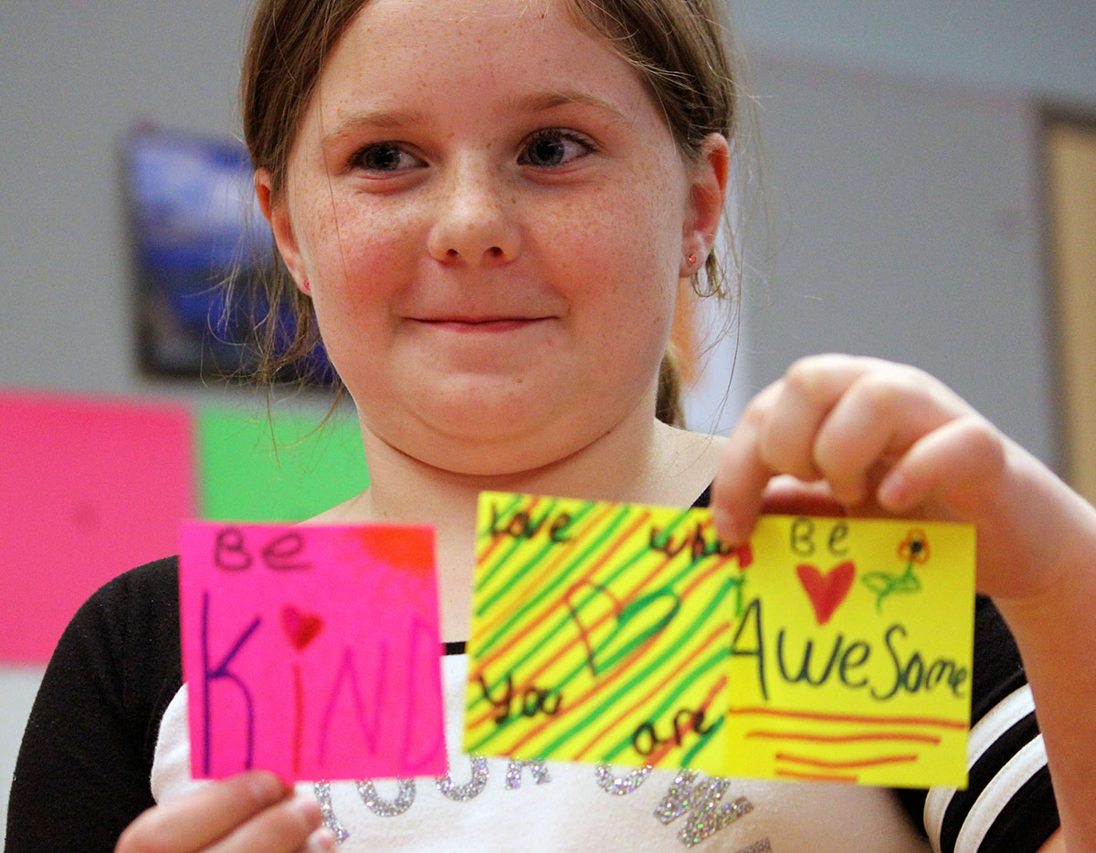 Henley Elementary School student and Kindness Club member Elliana Row holds up three notes she wrote for classmates.