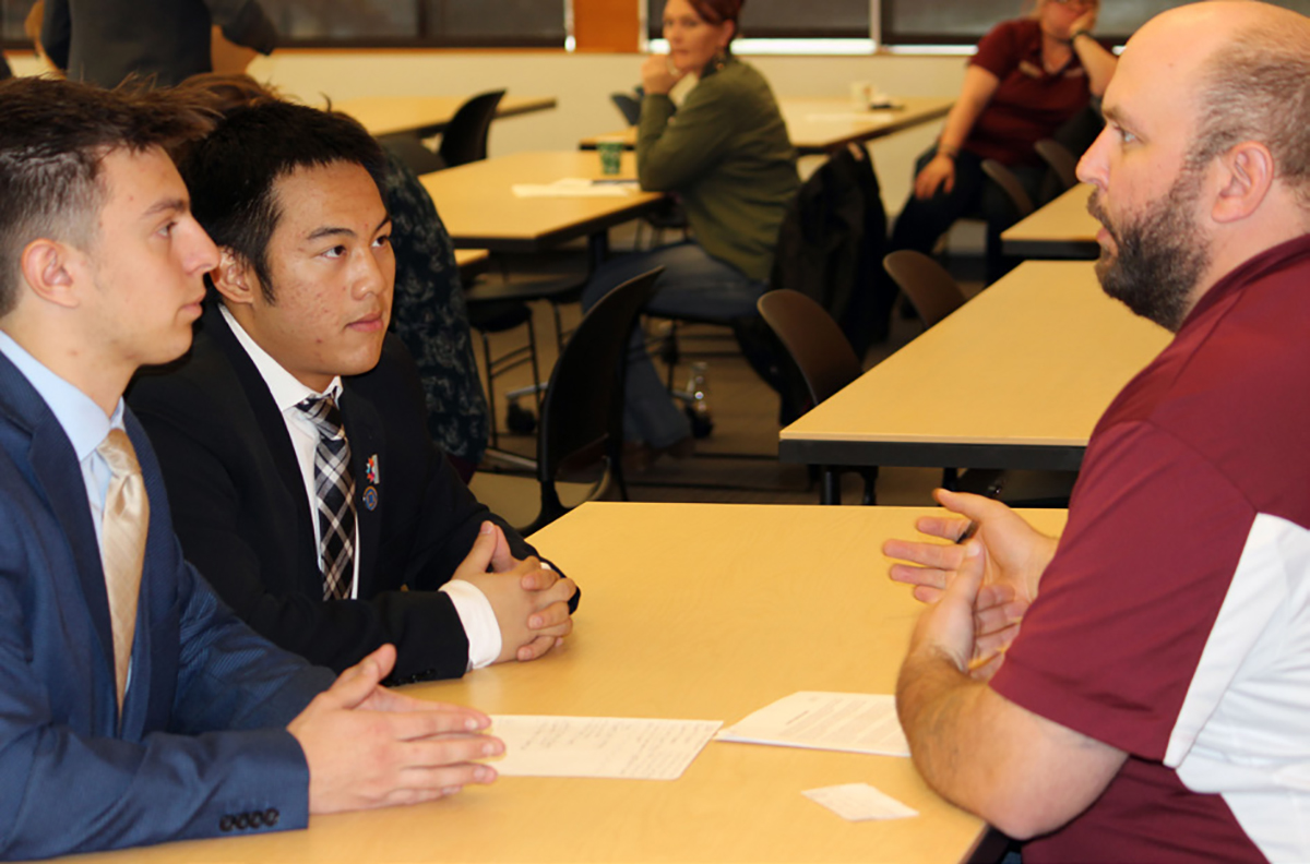 Henley HIgh School seniors Andrew Wilcher and Dylan Huynh compete in a DECA role play scenario Tuesday at the Business Skills Academy at Klamath Community College.