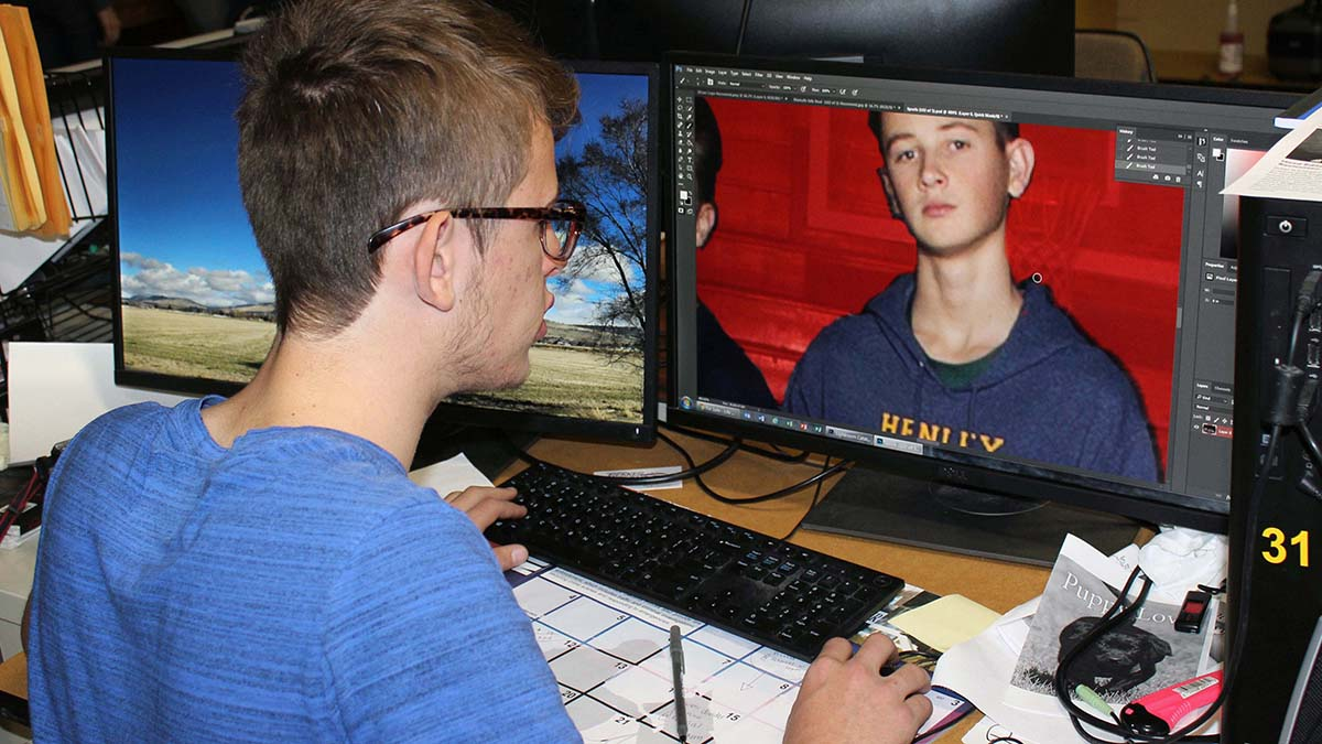 Zachary Cheyne-Russell, a student at Henley High School, edits a photo of classmate Colton Chenault for the school's yearbook during a media class. The media class is new offering at the school. In 2017-18, Henley High School had a four-year graduation rate of 99.30, one of the highest in the state and more than 20 percentage points higher than the state average.