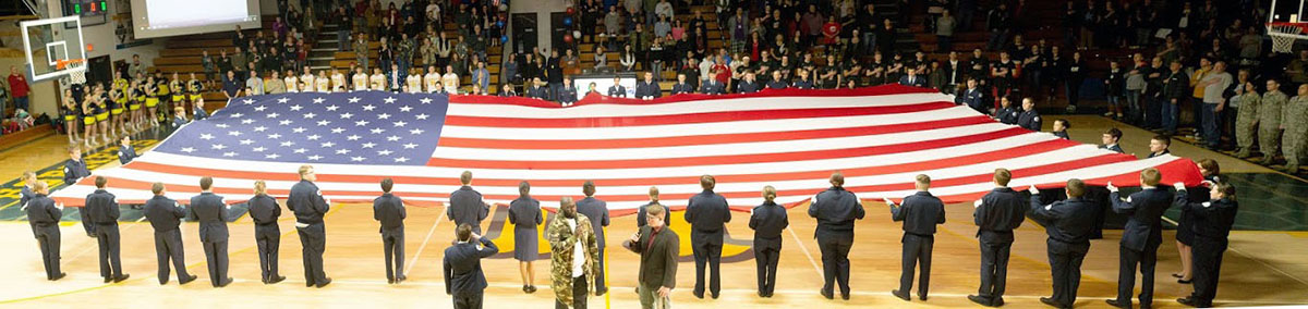 Members of Henley High School's 931st Air Force Junior ROTC unfurl and hold a 30-by-60 foot American flag while Henley choir teacher Chris Benjamin and Henley student Zach Marchessault sing a duet of the national anthem. (Photo by Carlos Becerra)