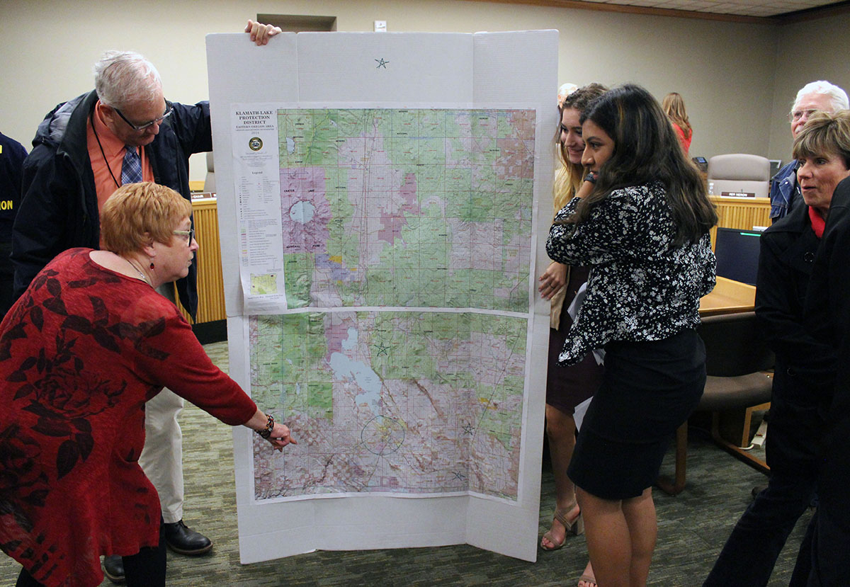 House Committee on Education Chair state Rep. Margaret Doherty looks at a large map KCSD students used during their testimony about a change in small high school funding. Holding the map is KCSD school board member Steve Lowell. Students Aurora Cerri and Irene Aguirre, both of Lost River, talk to Doherty.