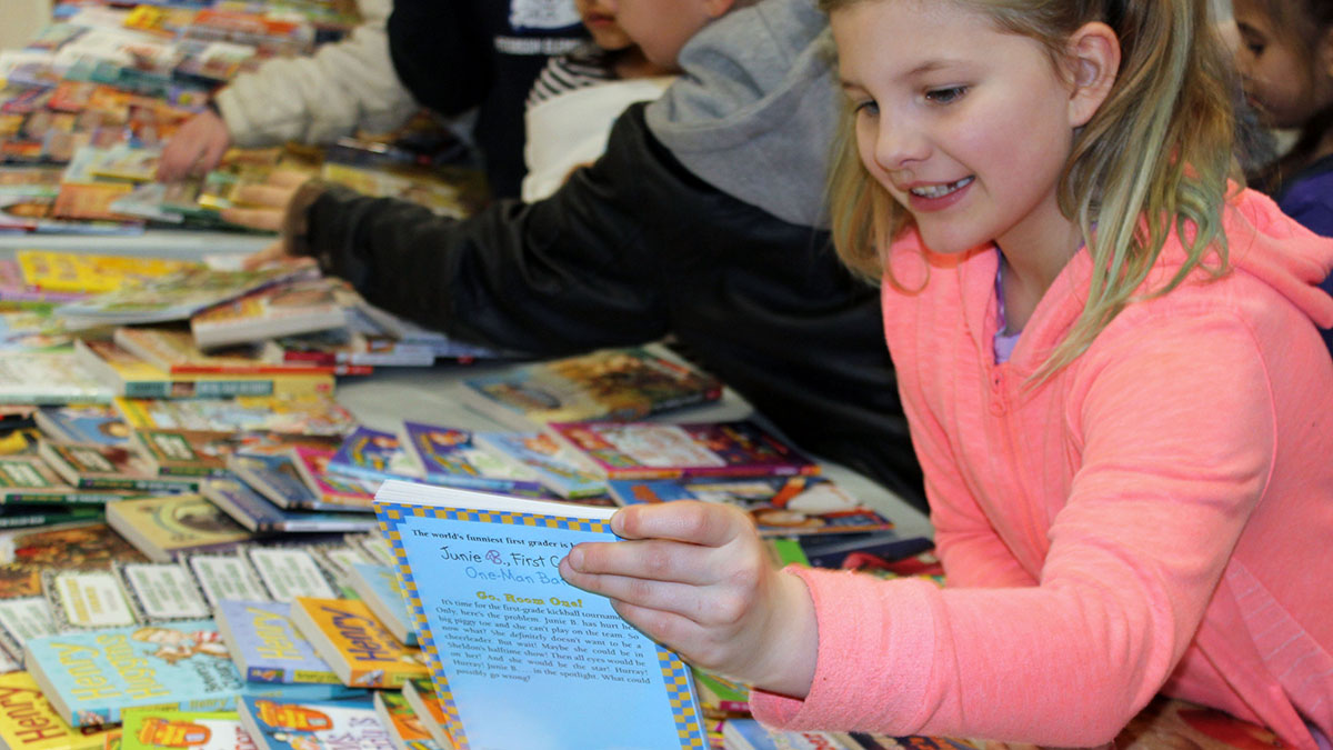 Peterson Elementary School fourth-grader Mikayla-Rose Mitchell picks out a free book to take home during the school's annual Family Literacy Night. (Image: Jennifer Hawkins)
