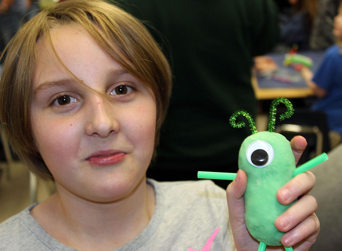 "Emma Van Leuven poses with her ""monster"" following a creative activity during Peterson's Family Literacy Night. (Image: Jennifer Hawkins)"