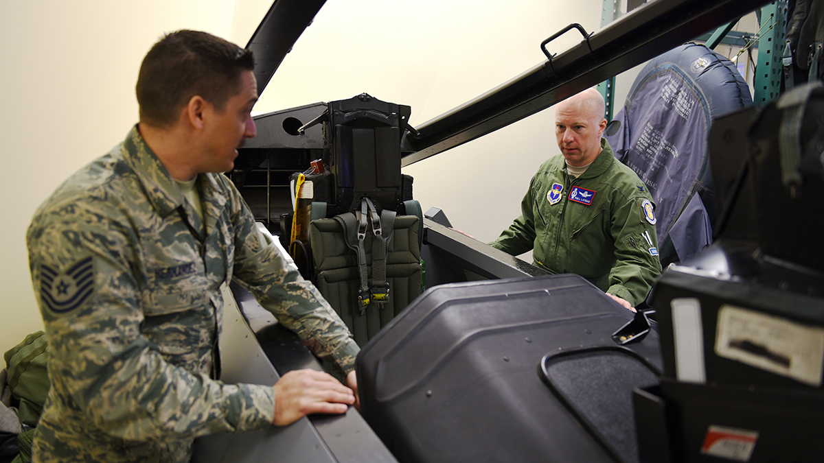 U.S. Air Force Tech. Sergeant Christopher Hernandez, 173rd Fighter Wing Aircrew Flight Equipment, instructs Col. Phillip Layman, Air Force Inspection Agency, on egress procedures in preperation for Layman's flight in an F-15C during the 173rd FW Unit Effectiveness Inspection capstone event April 6, 2019 at Kingsley Field in Klamath Falls, Oregon. The capstone inspection is culmination of on ongoing virtual inspection on the effectiveness of the unit through four major graded areas—managing resources, leading people, improving the unit, and executing the mission. (U.S. Air National Guard photo by Airman 1st Class Adam Smith)