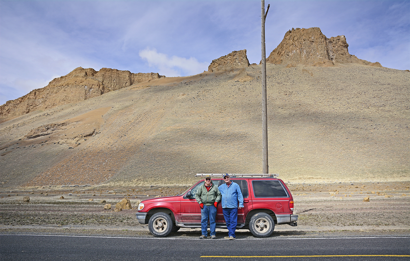 Cy Phillips (left) and friend Dennis Chabot pose in front of his red ford Explorer after checking on kestrel boxes on the eastern side of Tule Lake National Wildlife Refuge. Credit: Jon Myatt/USFWS