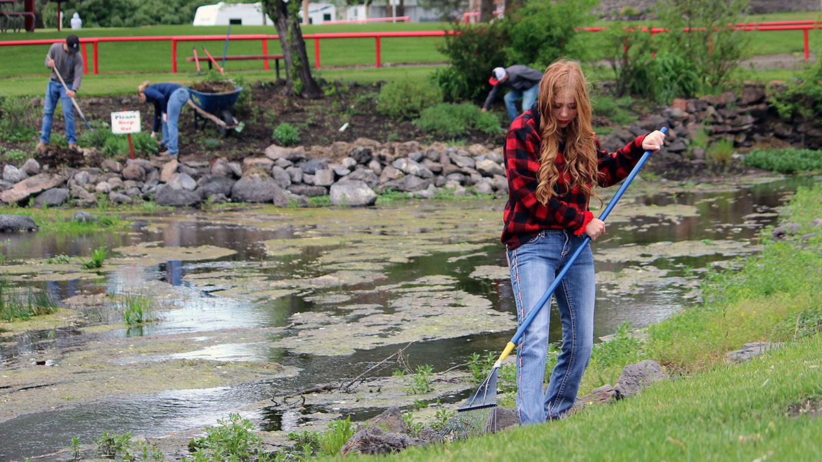 Haylee Hansen, a senior at Bonanza Junior-Senior High School, cleans up around the natural springs at Big Springs Park in Bonanza.