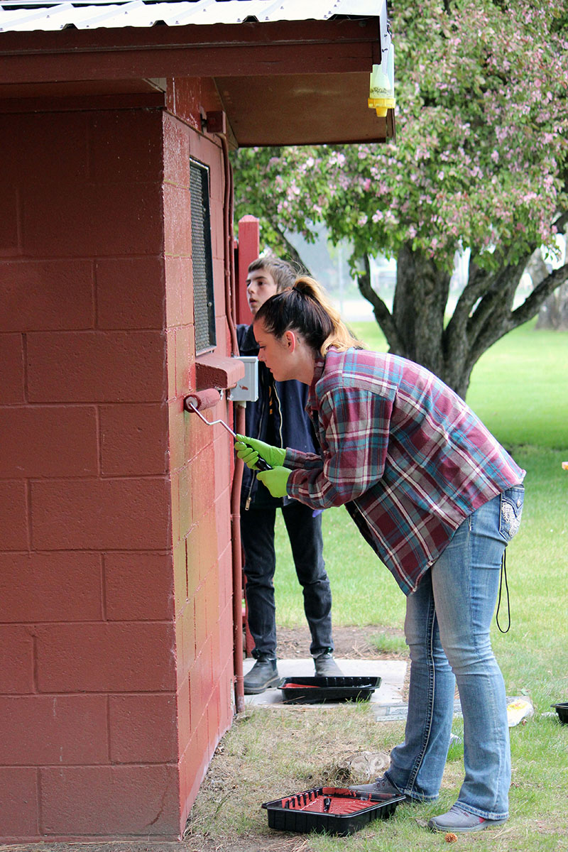 Bonanza high school students repaint the restroom walls at Big Springs Park on Thursday as part of an annual Give Back Day event.