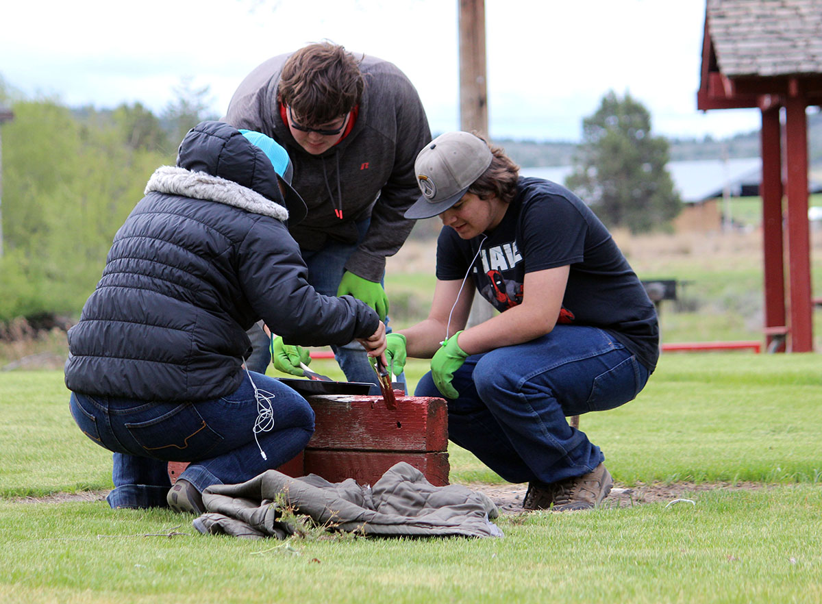 Bonanza high school student weed and repaint horseshoe pits at at Big Springs Park on Thursday as part of an annual Give Back Day event.