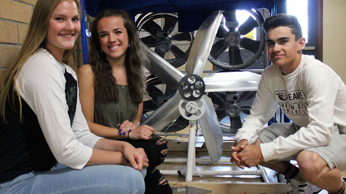 Henley High School students Grace Parker, Alyssa Michaelis and Skyler Howard pose with the wind turbine they designed. The team will compete next week at the National KidWind Challenge in Houston. (Not pictured: Team member Tim Orr)