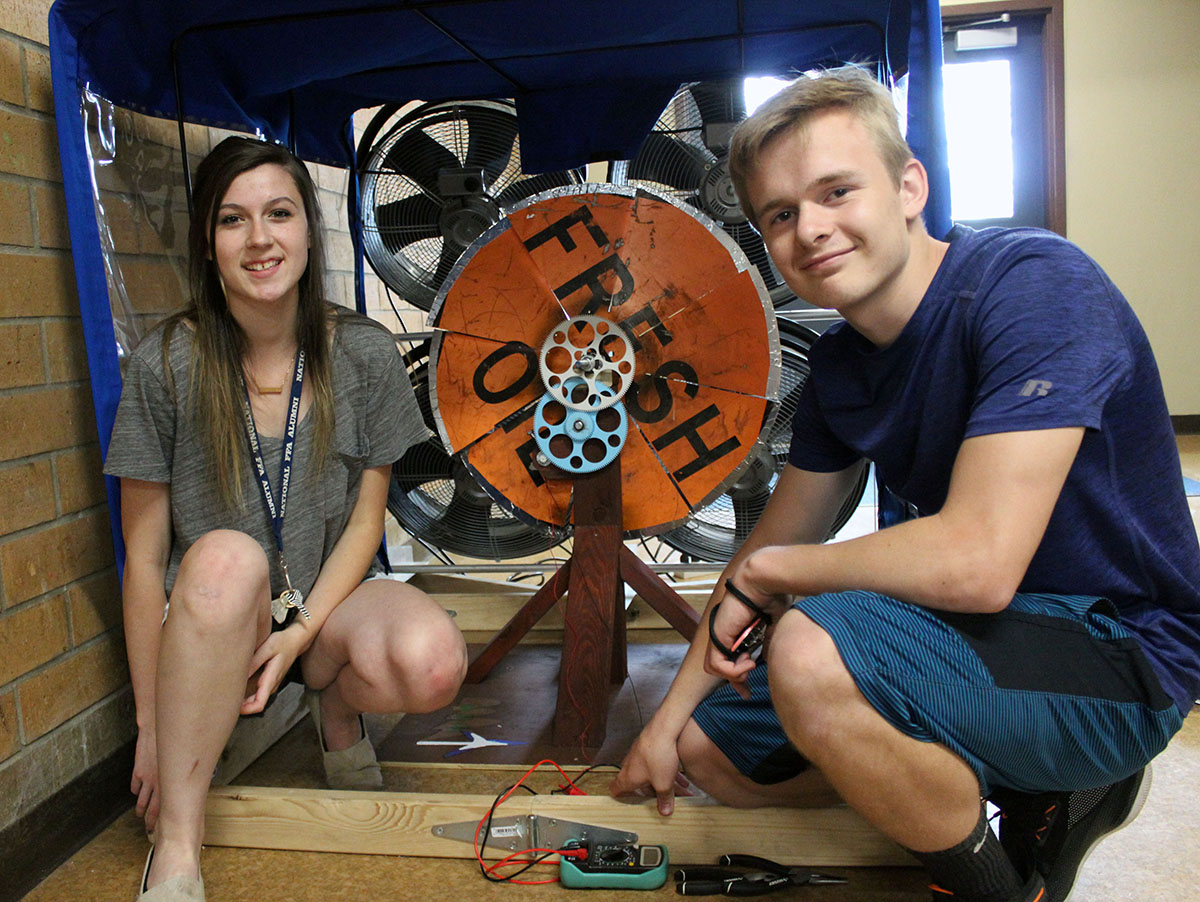 "The Henley High School team of Sam Ellis and Avery Hirschbock pose with their turbine. They created the blades from a ""fresh oil"" sign. (Not pictured Team Member Alex Sharp)"
