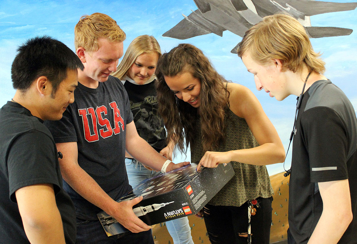 Henley High School engineering students Dylan Huhyn, Thys deHoop, Grace Parker, Alyssa Michaelis and MIchael Malineaux examine a Lego model of the Saturn V rocket donated by James Loftus of JPLMuseum.