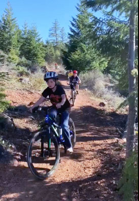 Members of Shasta Elementary School's mountain bike club ride down the trails at Shoalwater Bay.