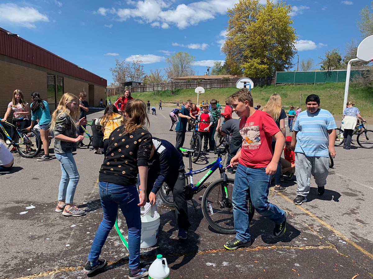 Members of Shasta Elementary School's mountain bike club clean off their bikes after a muddy ride.