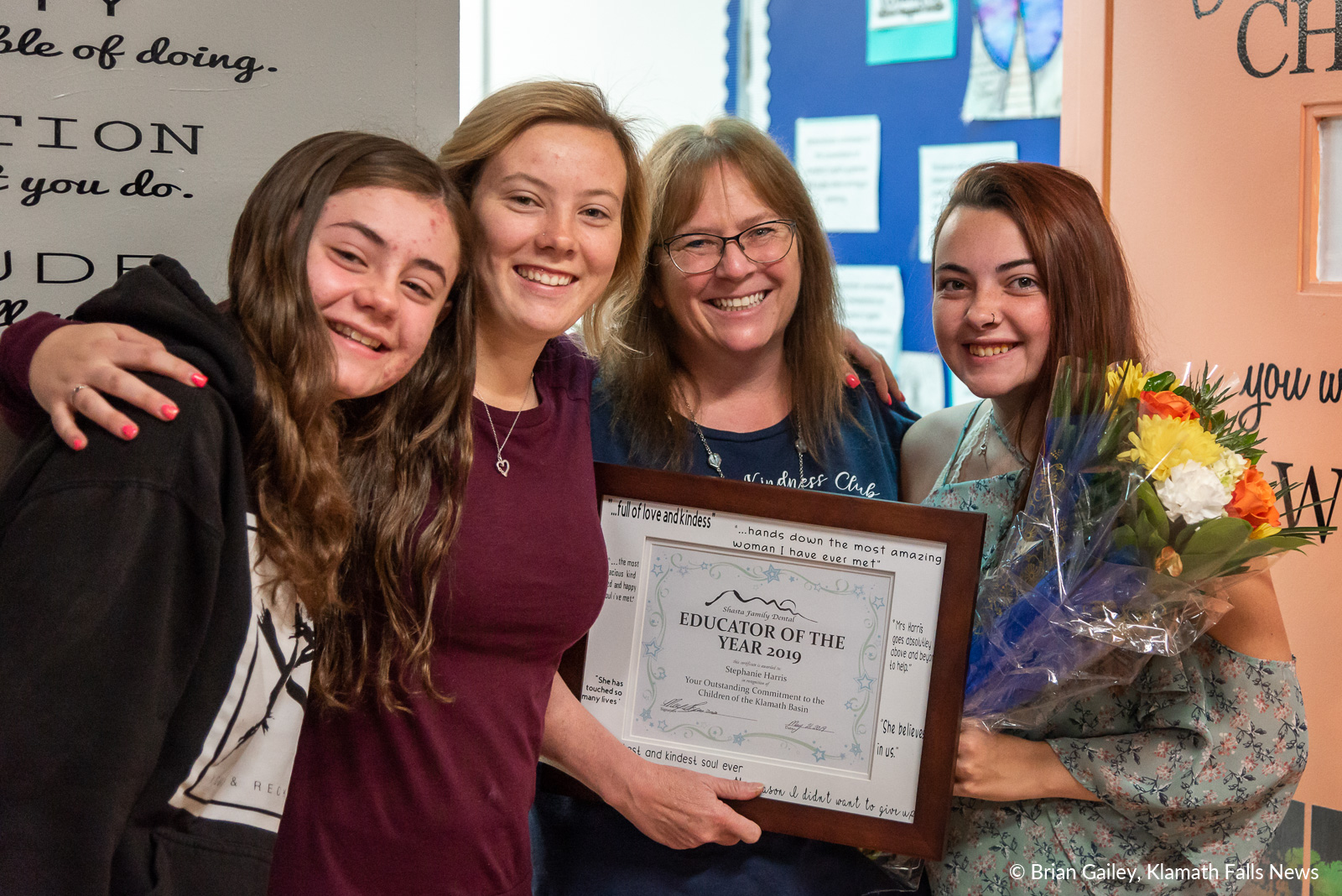 Stephanie Harris stands with a few of here students after being awarded Educator of the Year. Left to right: Brianna Drake, Hailey Nelson, Stephanie Harris, Kara LaMere. May 24, 2019 (Image, Brian Gailey / Klamath Falls News)