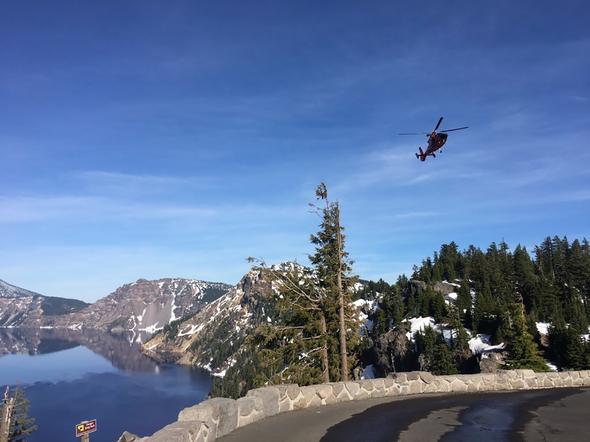 An MH-65 Dolphin helicopter aircrew, from Coast Guard Sector North Bend, flies over Crater Lake National Park, June 10, 2019. The aircrew was in the area to assist National Park Service personnel rescue a man who fell 800 feet down into the caldera of Crater Lake. U.S. Coast Guard photo courtesy of Sector North Bend.