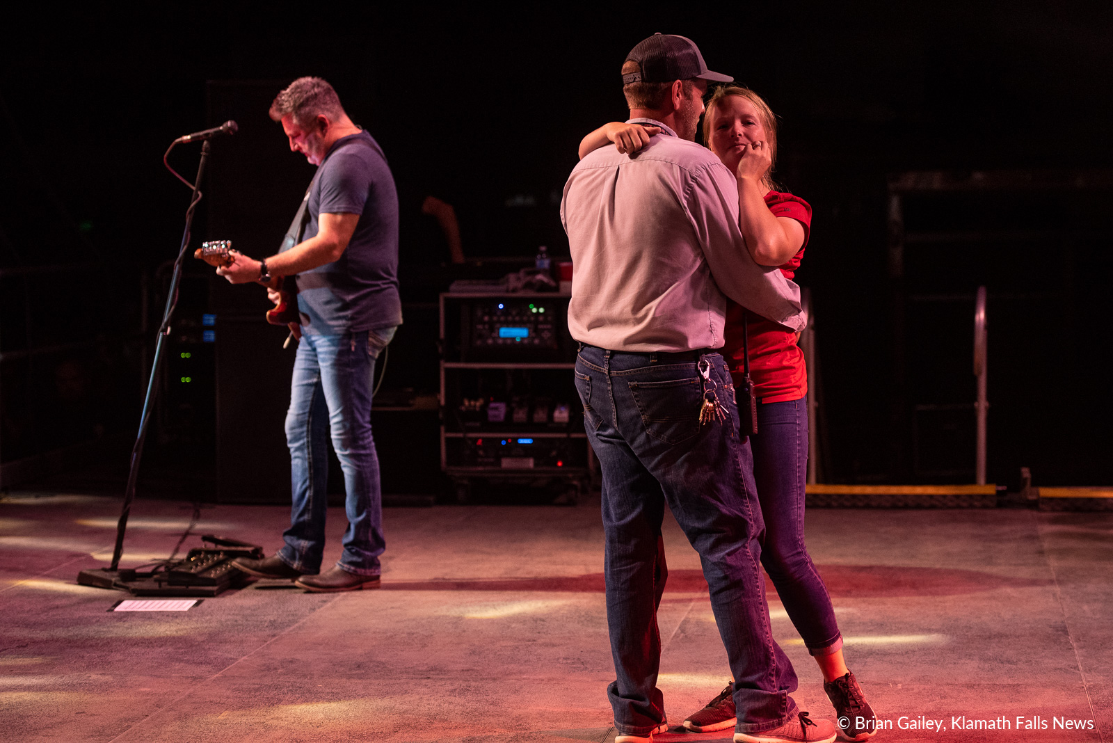 Drew Patzke, a Klamath County Fairgrounds maintenance employee dances with his new fiance, Kaitlin Collom on stage as Lonestar plays Amazed. Patzke proposed to Collom moments earlier on stage with the help of Lonestar. August 3, 2019. (Image, Brian Gailey / Klamath Falls News)