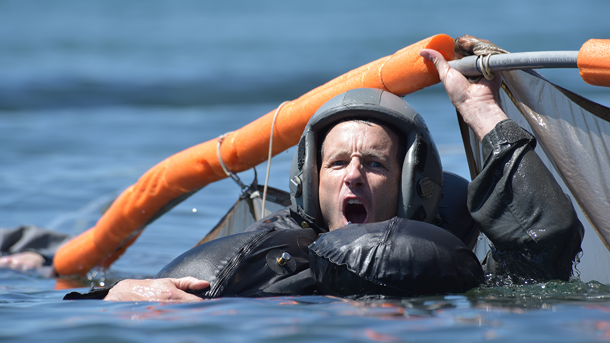 U.S. Air Force Lt. Col. Kedric Osborne, an F-15C Instructor Pilot at the 173rd Fighter Wing, takes a deep breath before submerging beneath a floating parachute canopy during water survival training at Cultus Lake, Oregon, July 25, 2019. Aircrew Flight Equipment hosted the training and was present for all the iterations to ensure participant safety and to ensure participants received the necessary training in the event of an ejection over water. (U.S. Air National Guard photo by Master Sgt. Jefferson Thompson)