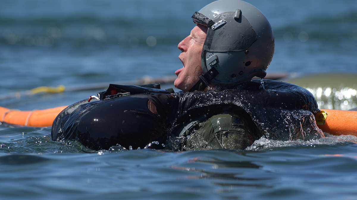 U.S. Air Force Lt. Col. Earnest O'Neal, a flight surgeon at the 173rd Fighter Wing, grabs a breath after finding his way from under a floating parachute canopy during water survival training at Cultus Lake, Oregon, July 25, 2019. The training occurs every three years and is necessary for flying and training the F-15C over water, something these pilots do when using the ranges over the Oregon and California Coast. (U.S. Air National Guard photo by Master Sgt. Jefferson Thompson)