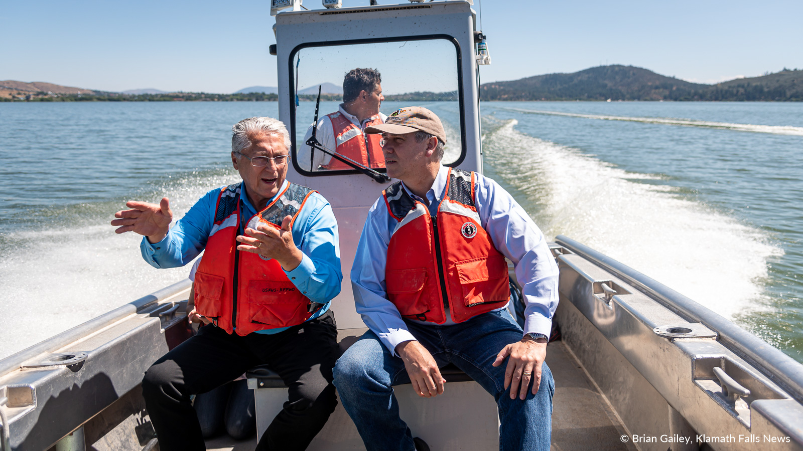 Klamath Tribes Chairman, Don Gentry (left) discusses suckerfish with US Senator Jeff Merkley (right) while heading up Upper Klamath Lake to view the US Fish and Wildlife's floating net pens.August 12, 2019 (Image, Brian Gailey / Klamath Falls News)