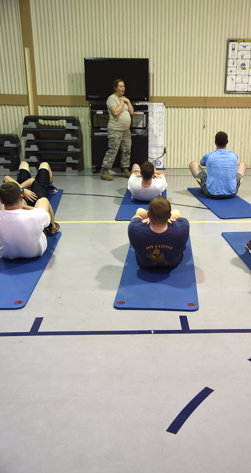 U.S. Air Force Tech. Sgt. Rachel Warnick, a Community Health and Wellness Center human performance specialist at the 173rd Fighter Wing, teaches a group of assembled Airmen about proper form for sit-ups, Sept. 7, 2019. The class falls under the purview of a new health and wellness initiative at Kingsley Field in Klamath Falls, Oregon. (U.S. Air National Guard photo by Tech. Sgt. Jason van Mourik)