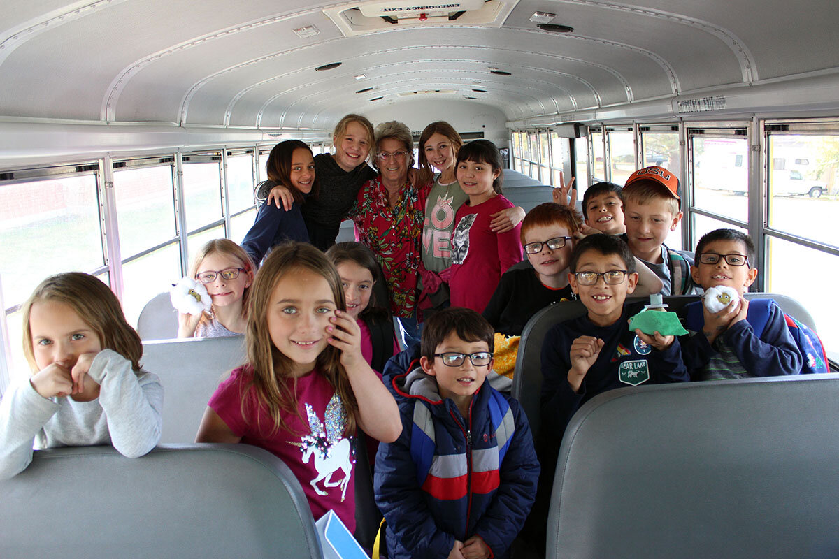 Davida Croy poses with Merrill Elementary School students who she transports to and from school every day. After 28 years driving bus, she is on her third generation of families in the Lost River area.