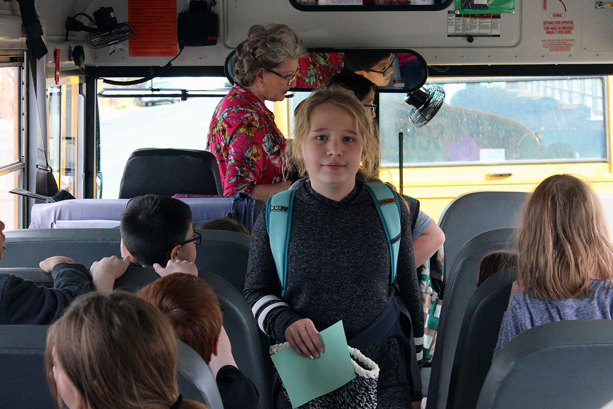 Merrill Elementary student Isabelle Herring gets on Davida Croy's bus at the end of her school day.