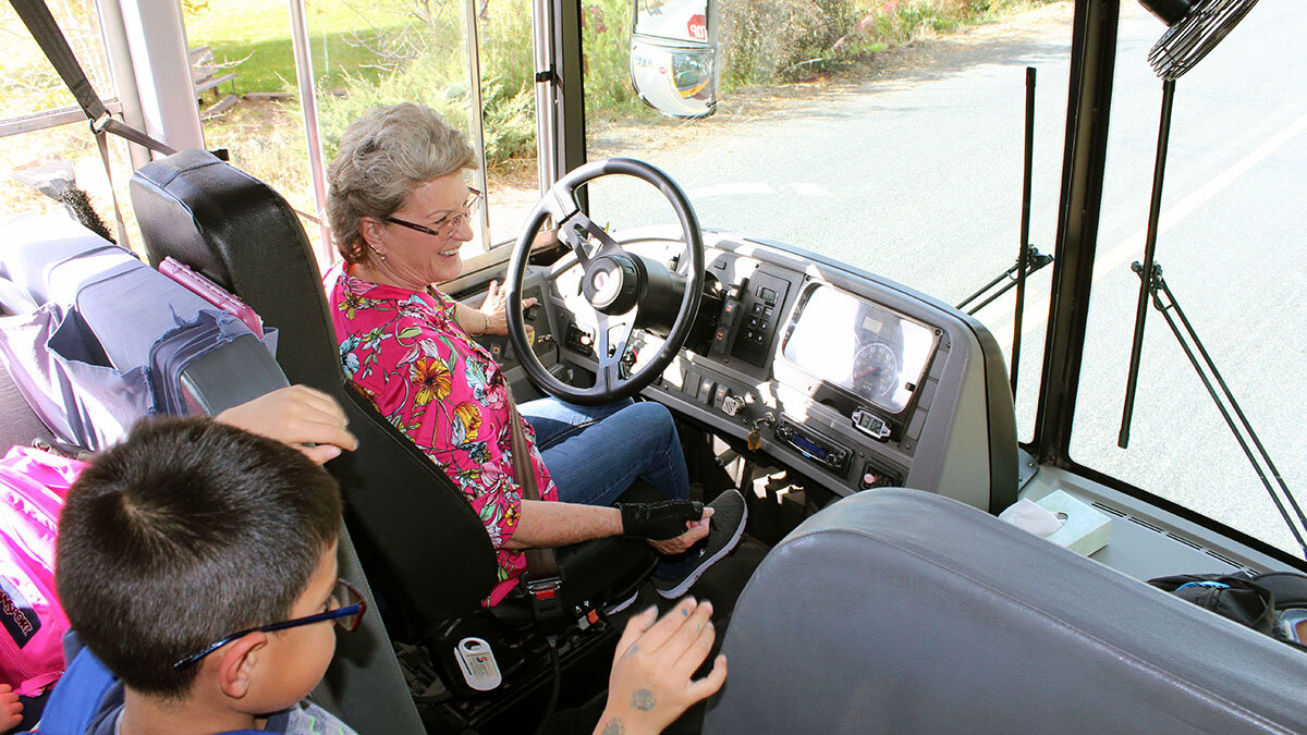 Davida Croy smiles as Merrill Elementary School students get off the bus at the end of their school day.
