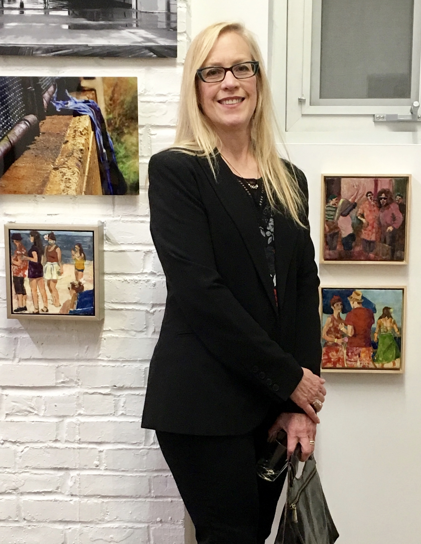 The artist pictured with 3 encaustics among other work at Open Orange.