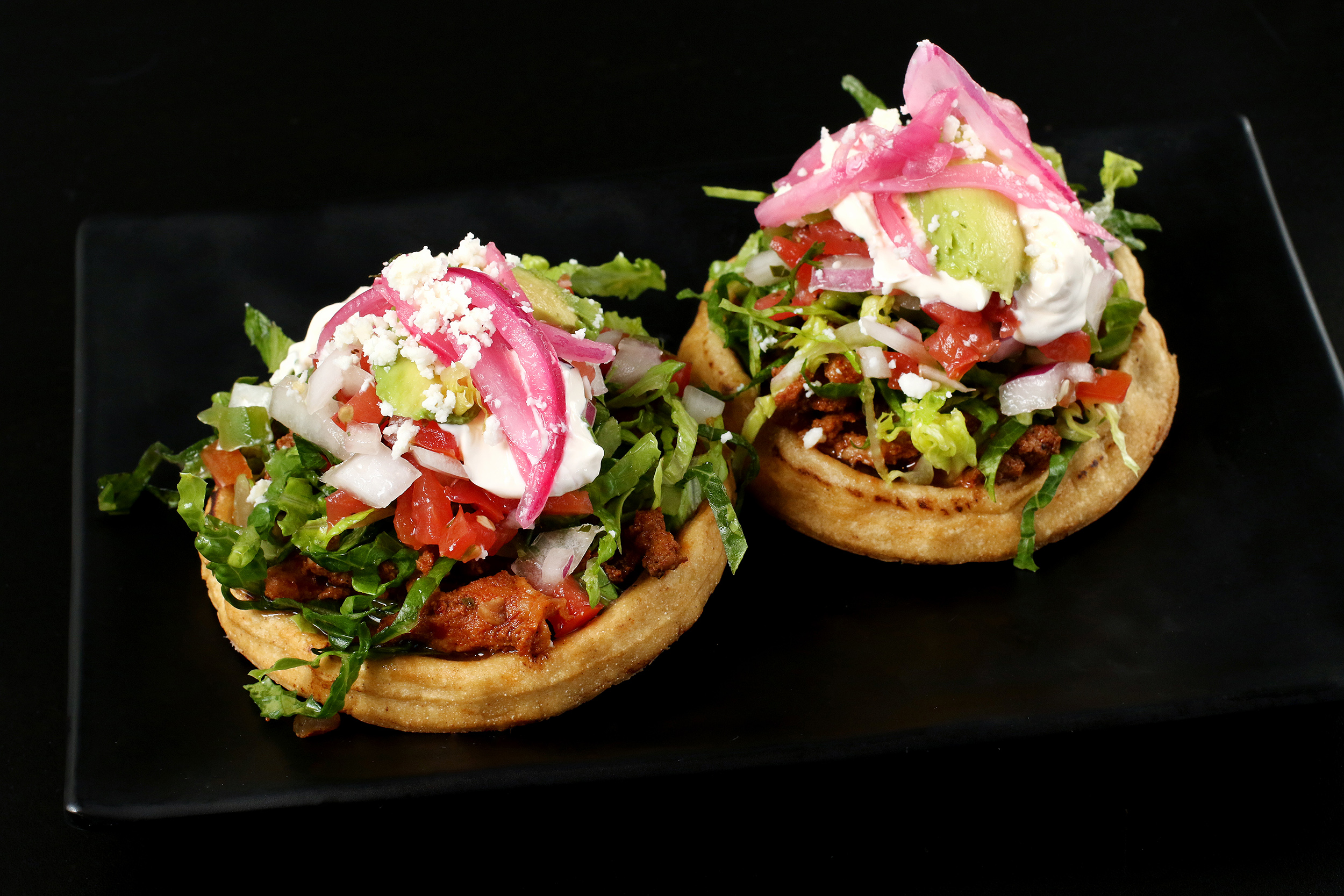 Pork on Top of Fried Masa with Lettuce and Pickled Red Onion