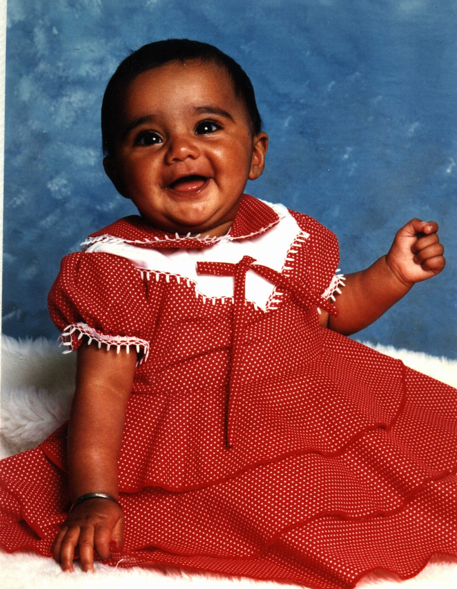 Suki's first daughter rocking a red frilly dress and smile.