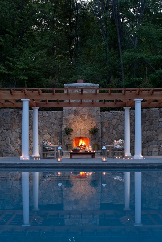 Poolside outdoor fireplace at night
